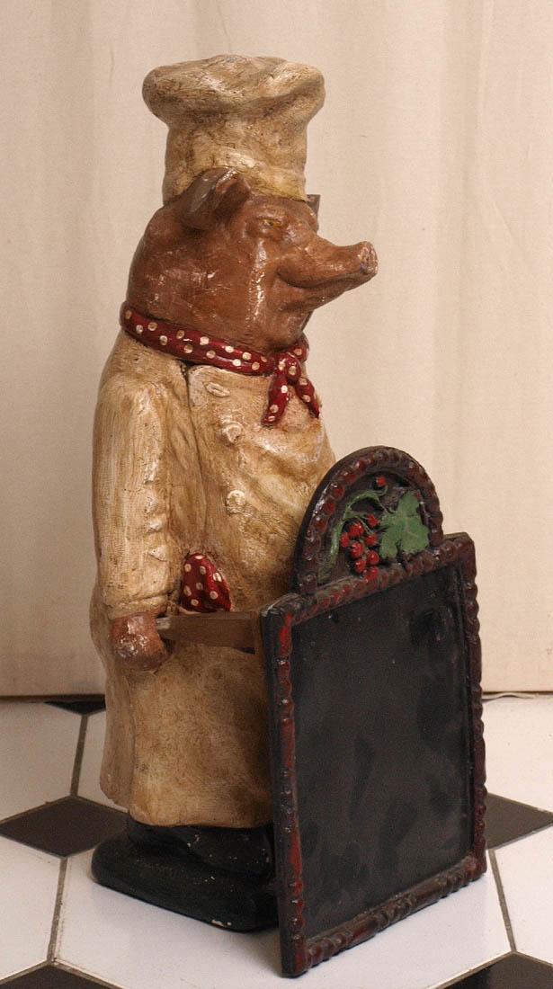 Los 32 - Thekenaufsteller In Form eines Schweines in Kochmontur, mit den Händen eine Tafel haltend. Gips,
