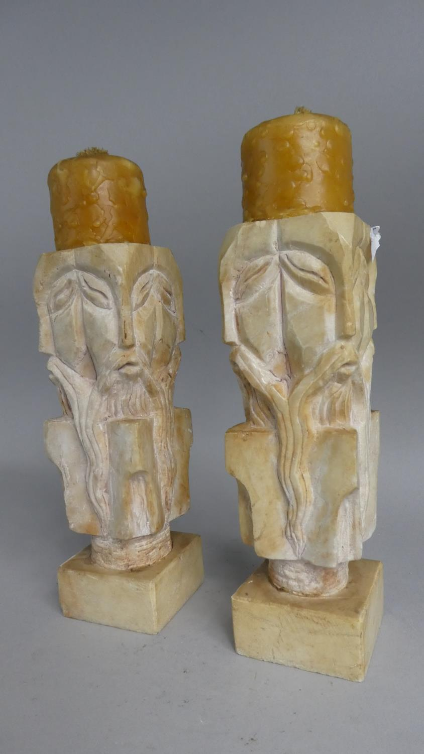 Lot 75 - A Pair of Modern Carved Stone Candlesticks each with Four Side Masks, 24cm High