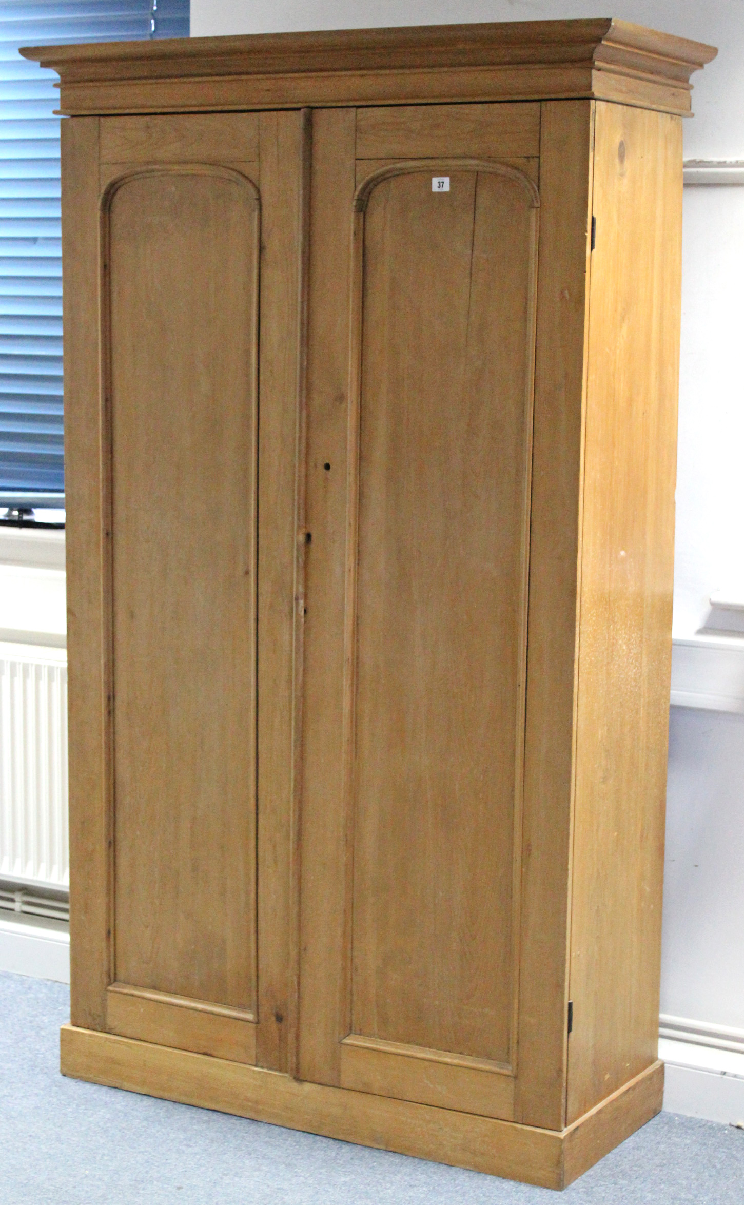 Lot 37 - A pine wardrobe with hanging compartment above a long drawer enclosed by pair of panel doors; & on