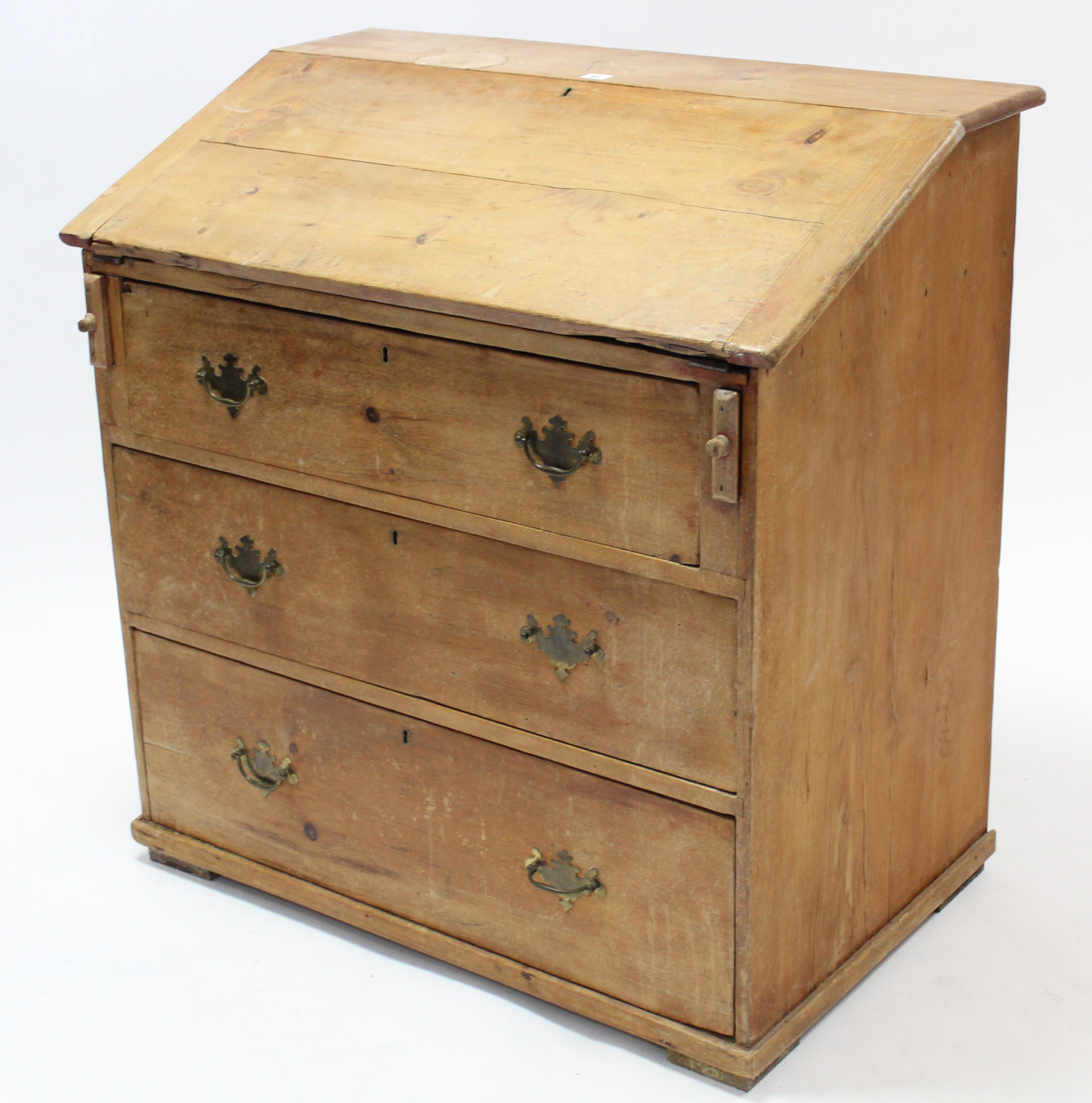 Lot 41 - A pine bureau with fitted interior enclosed by fall-front above three long graduated drawers, & on