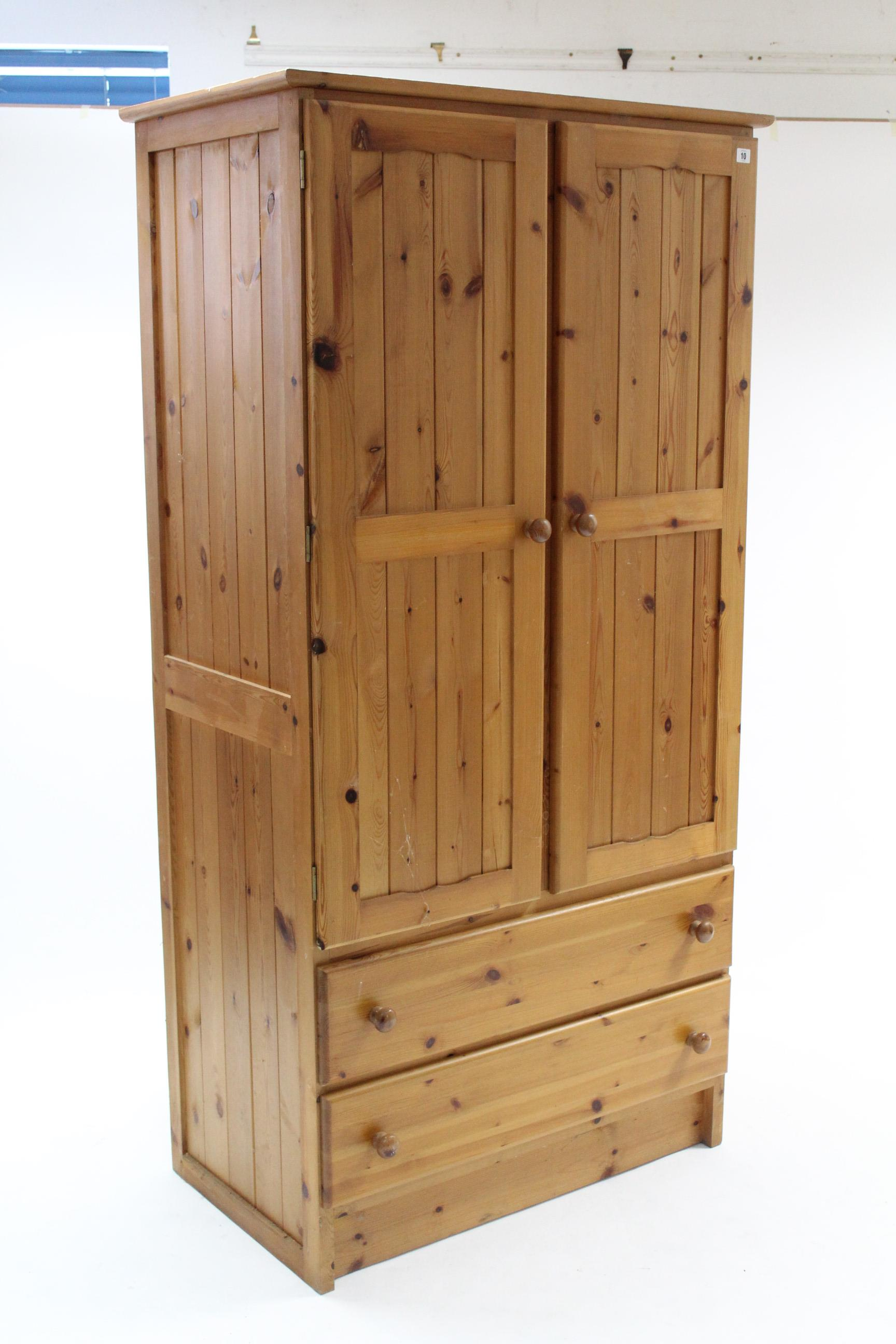 """Lot 10 - A pine wardrobe enclosed by pair of panel doors above two long drawers, 37¼"""" wide x 73"""" high."""