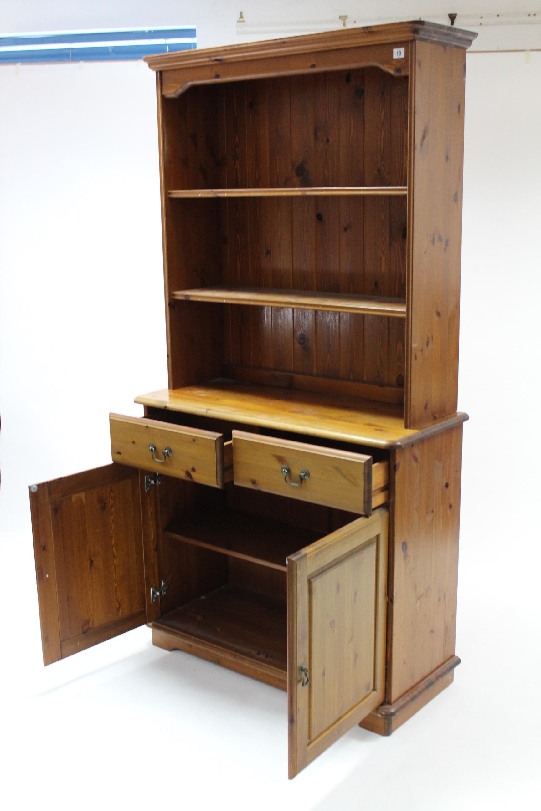 Lot 13 - A pine dresser the upper part fitted two open shelves & with panelled back, the base fitted two