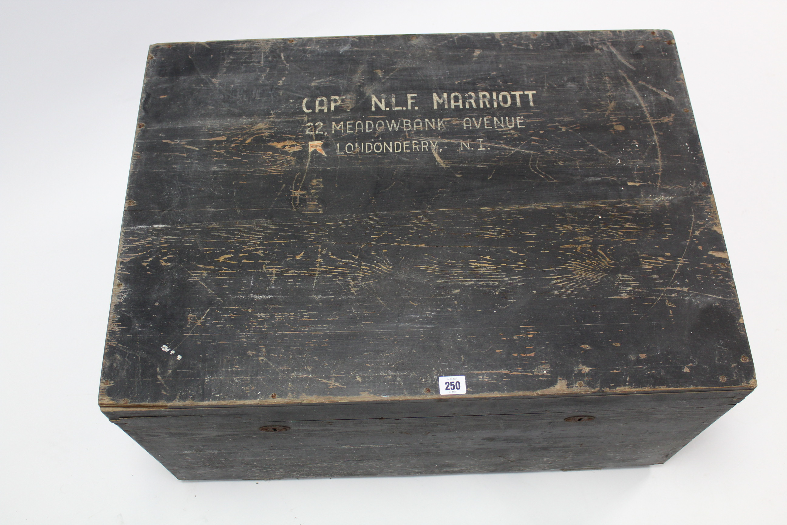 """Lot 250 - A mid-20th century black painted deal travelling trunk, the hinged lift-lid inscribed: """"CAPT. N."""