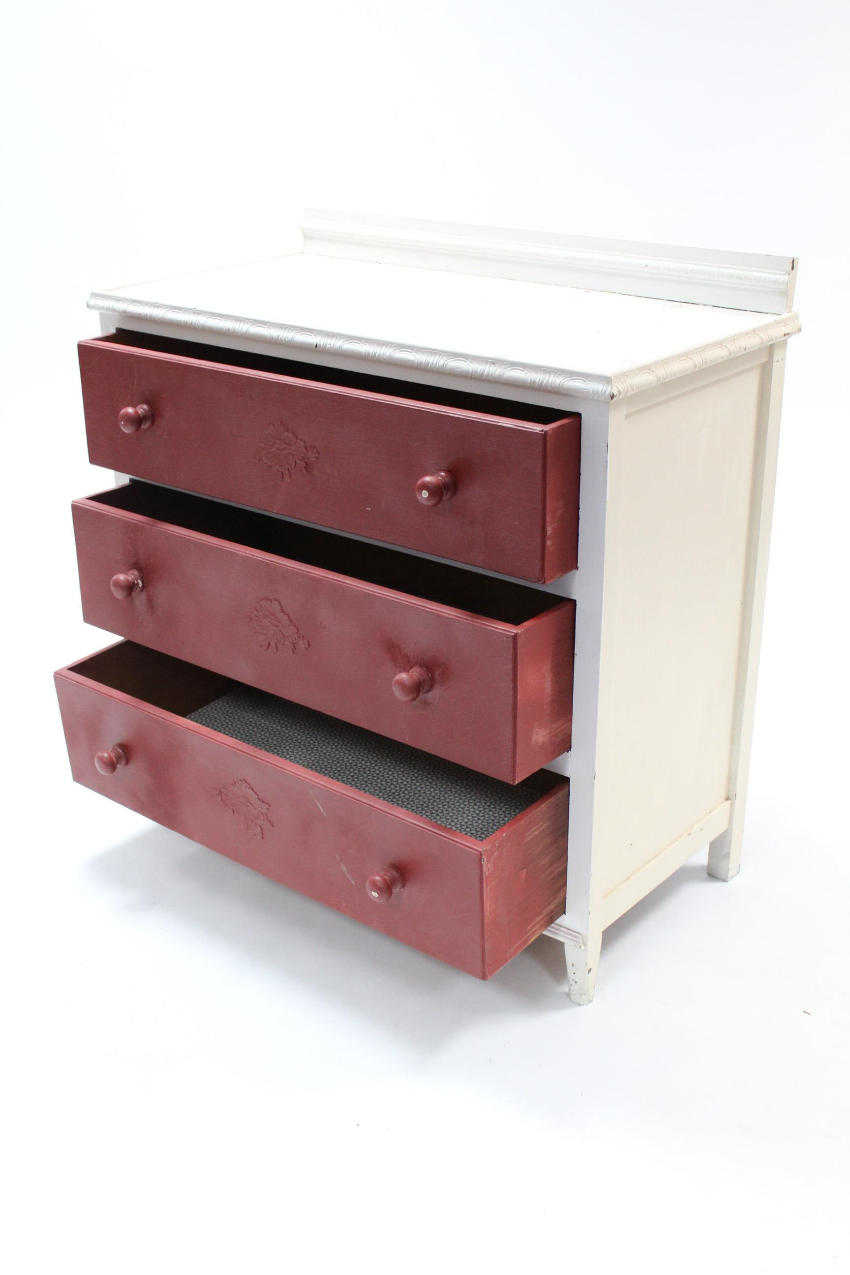 Lot 15 - A white & crimson painted oak small chest fitted three long drawers with turned knob handles, & on