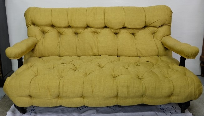 Lot 4 - Vicrian Ebonised Mahogany Framed Settee, deep butned with yellow fabric, sprung seat, on turned legs