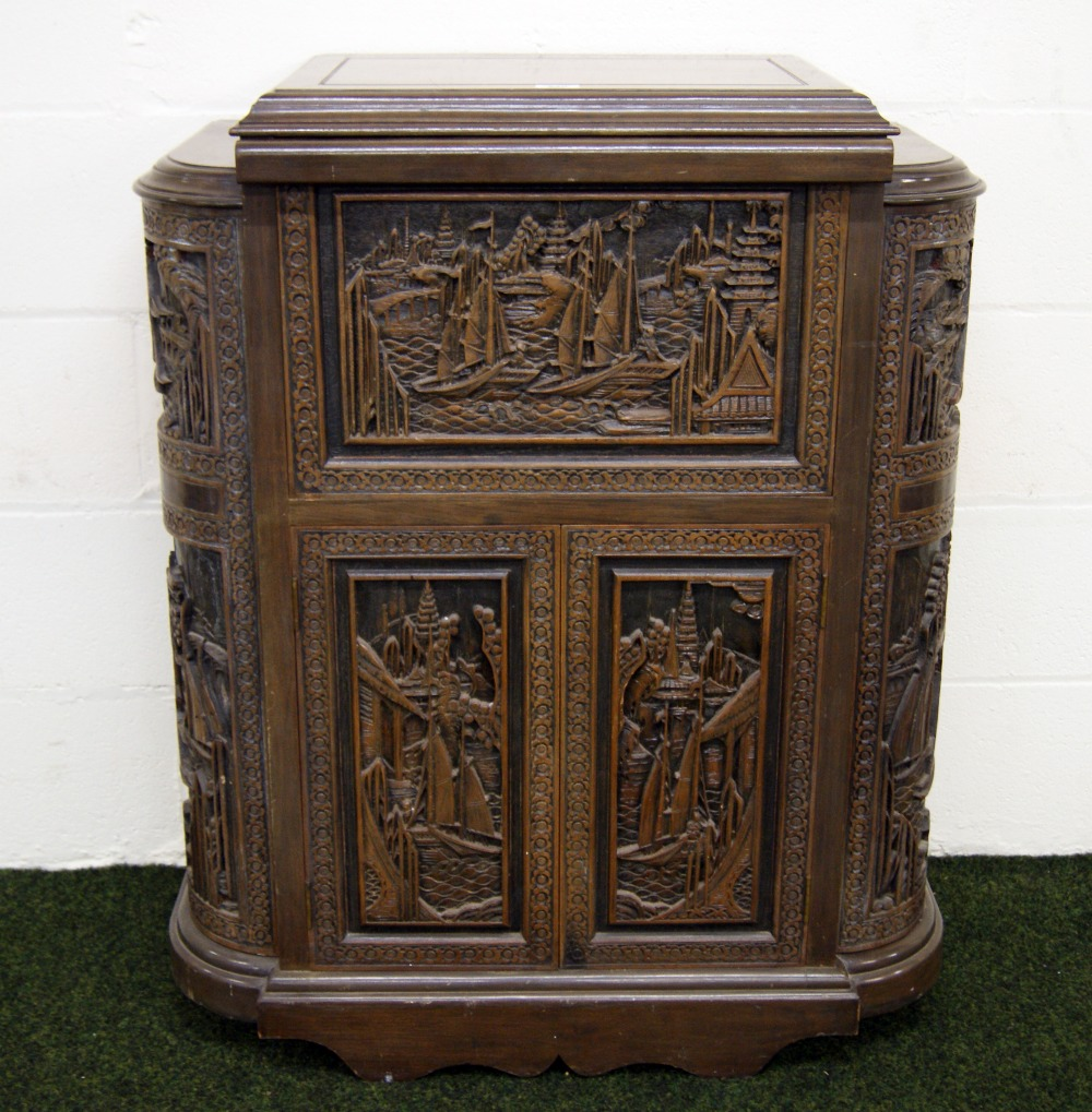 A heavily-carved Chinese camphor wood cocktail cabinet with lift ...