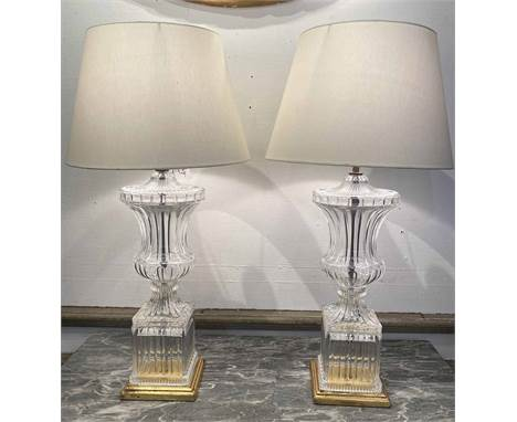 TABLE LAMPS, a pair, in the manner of Baccarat, moulded crystal glass urn design, on square stepped giltwood bases with silk