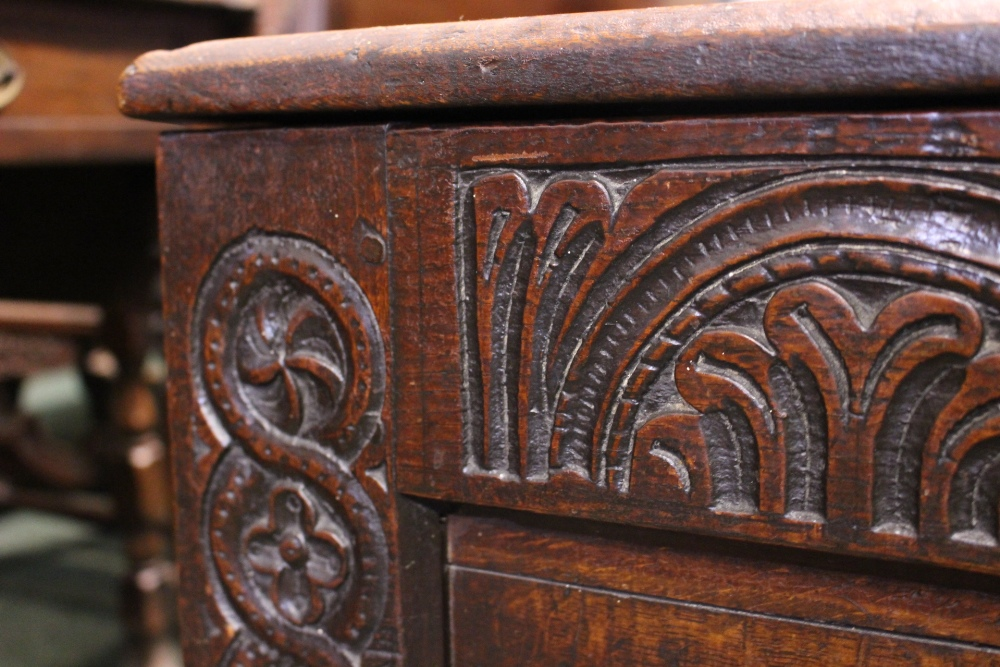 """Lot 42 - A 17TH CENTURY OAK """"COFFER""""/CHEST, with deep oak patination, below the lid runs a band of carved"""