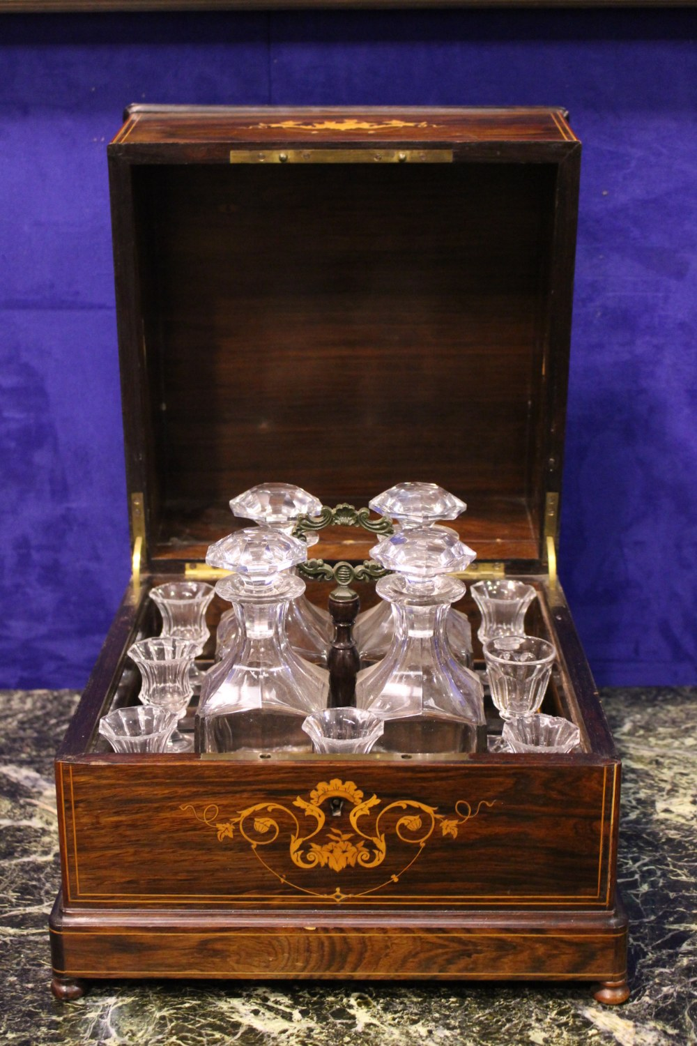 Lot 47 - A ROSEWOOD DECANTER BOX, with satinwood inlaid detail, hinged lid opens to reveal four cut glass