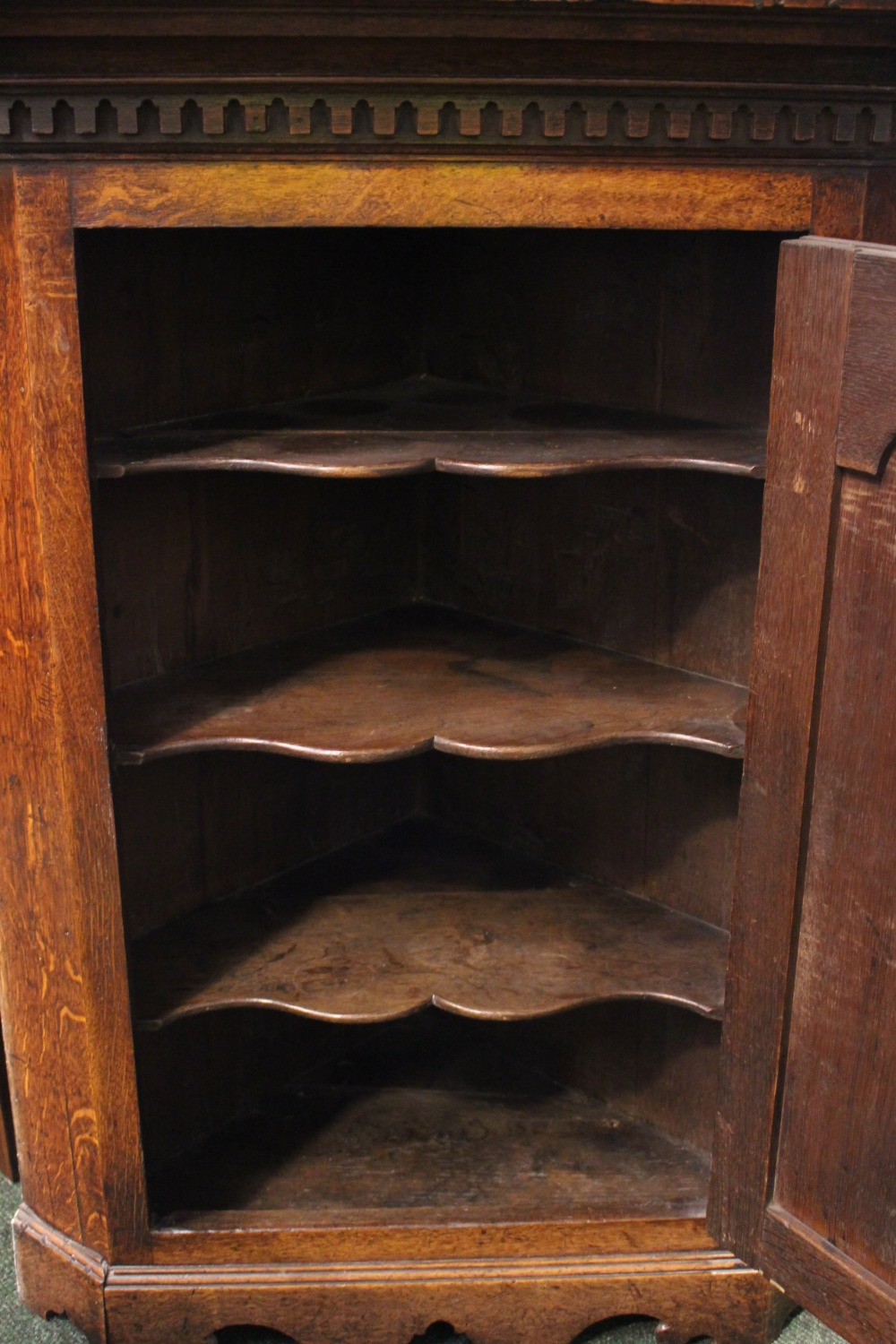 Lot 51 - AN OAK HANGING CORNER CUPBOARD, straight fronted, with fluted cornice over a carved panel door,