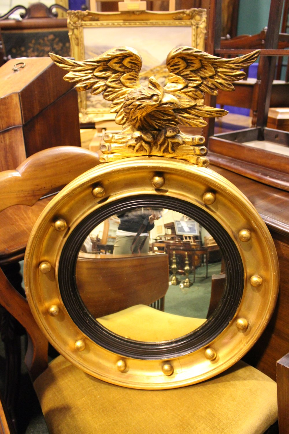 Lot 52 - A GILT WOOD REGENCY ROUND CONVEX MIRROR, with eagle mount, ebonised reeded slip