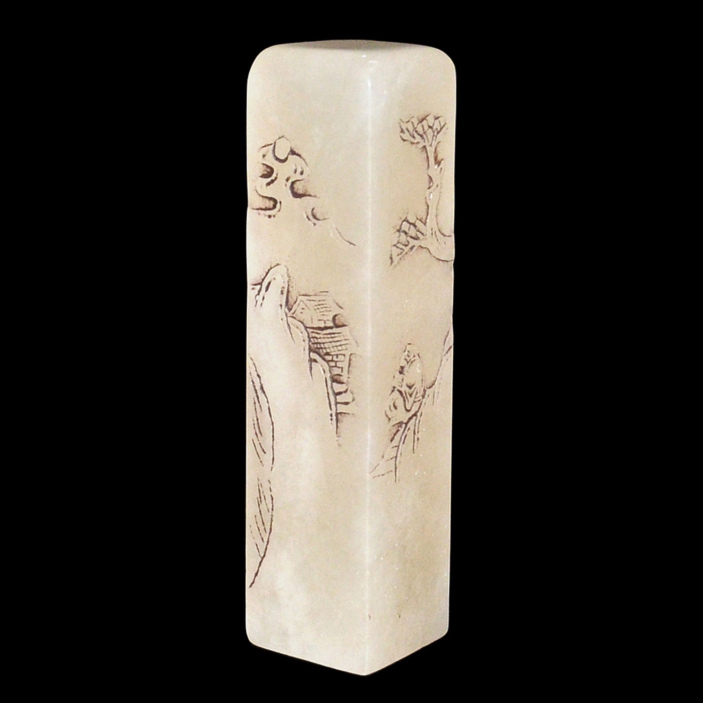 Lot 56 - 芙蓉石荔枝凍浮雕山水人物長印大方章 Translucent Furong Stone Columnar Seal Carved with Figural Landscape  Height: 5⅝