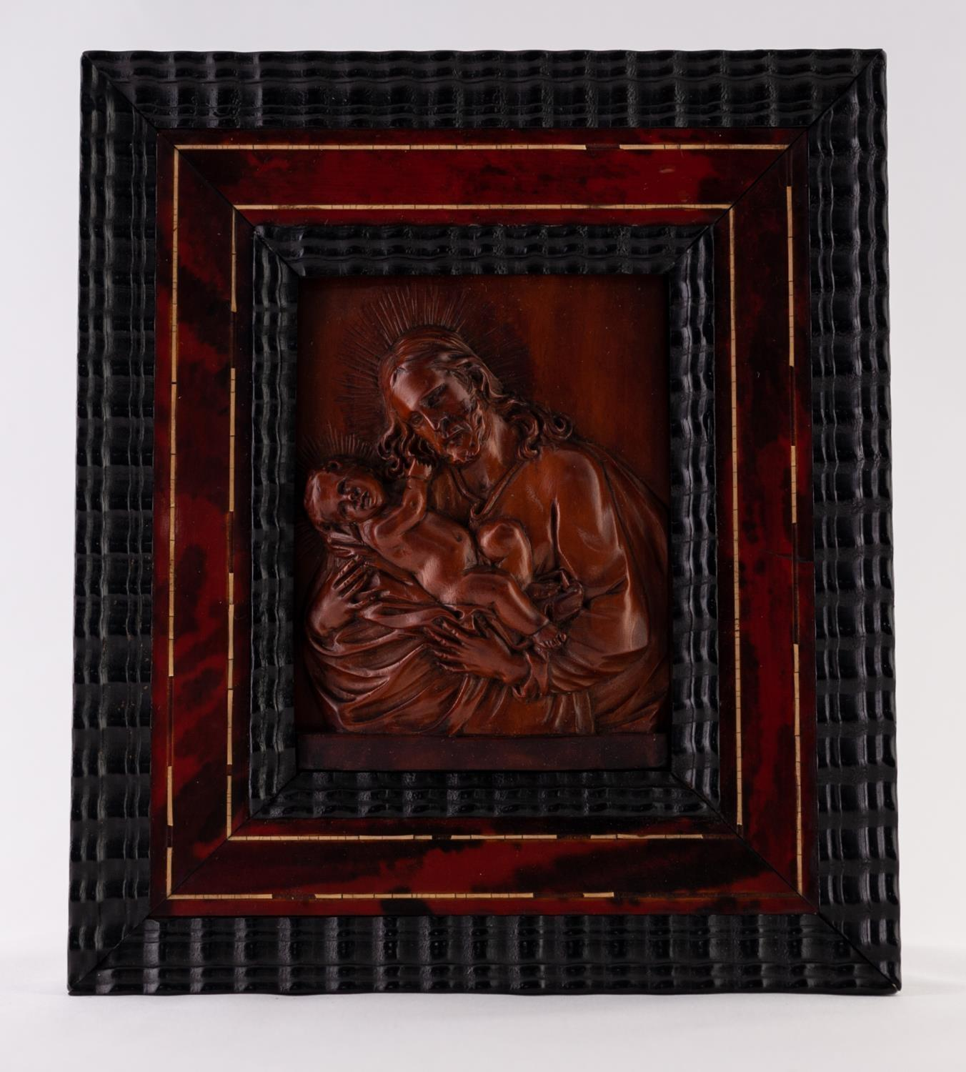 AN 18TH CENTURY FLEMISH CARVED FRUITWOOD RELIEF OF JOSEPH CRADLING THE CHRIST CHILD, contained