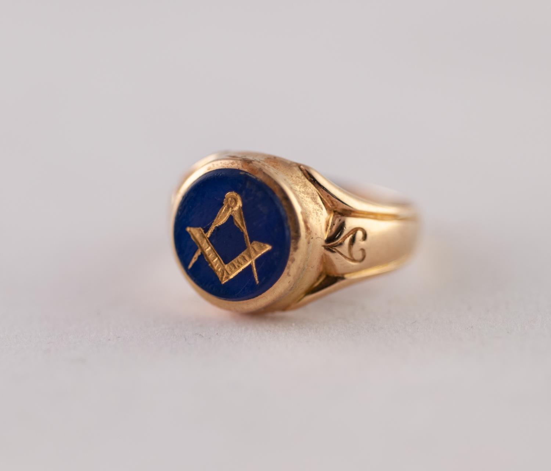 EDWARDIAN 18ct GOLD MASONIC INTAGLIO RING. A round blue glass intaglio with gilt Masonic motif, to