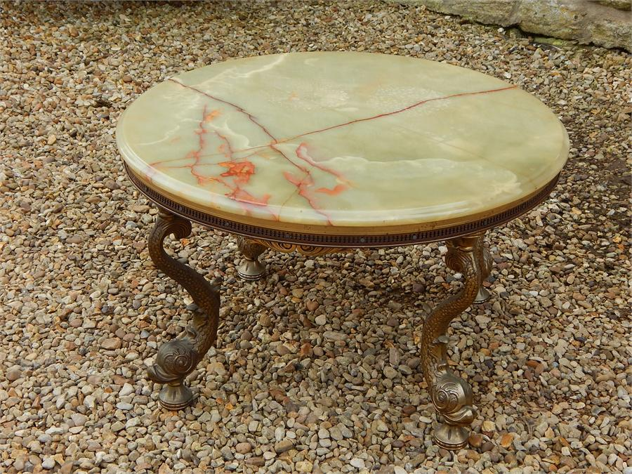 Lot 88 - Onyx and brass coffee table on brass stylised fish supports. ~