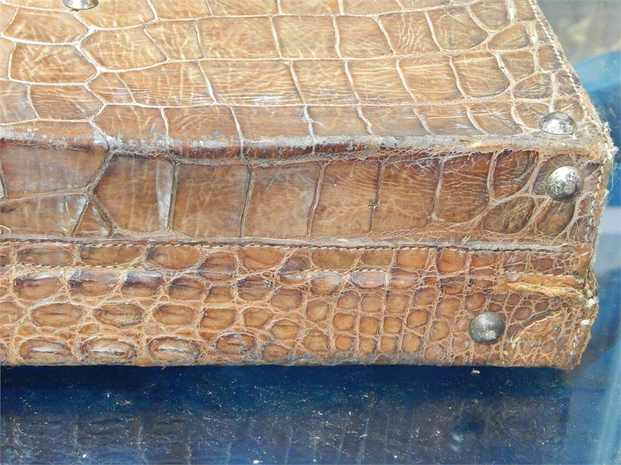 Lot 40 - Crocodile or alligator skin briefcase, sitting on brass stud supports - handle needs re-stitching