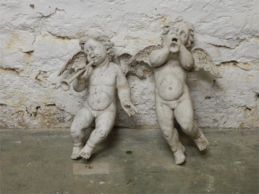 Lot 21 - A pair of winged stone-effect resin flying cherubs / putti. Modern