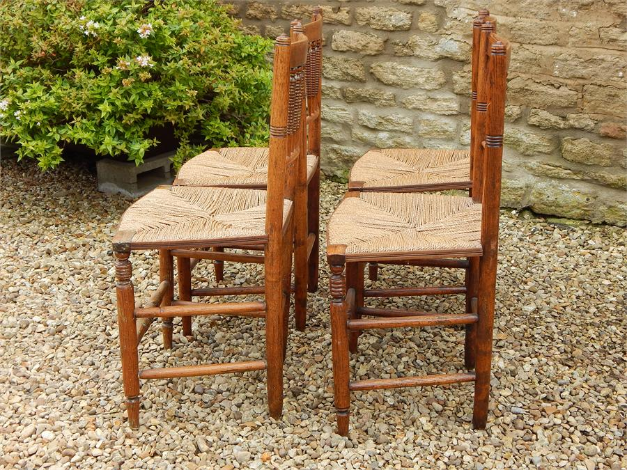Lot 77 - A Set of Four Matching Elm Country Kitchen Rush Seated Side Chairs, turned spindle Backs in a fan