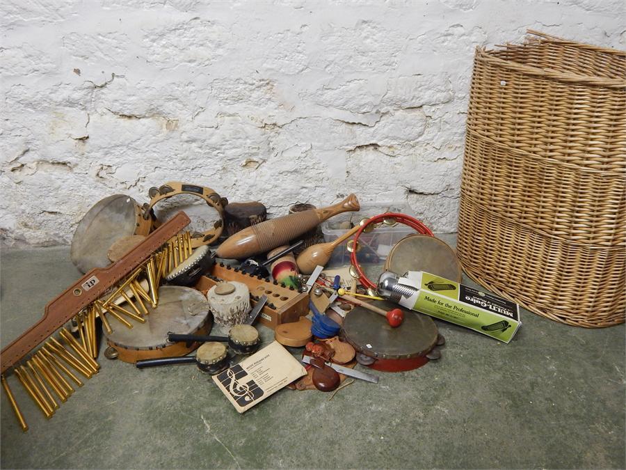 Lot 49 - Musical instruments, tambourines, multi guiro. In wicker basket.