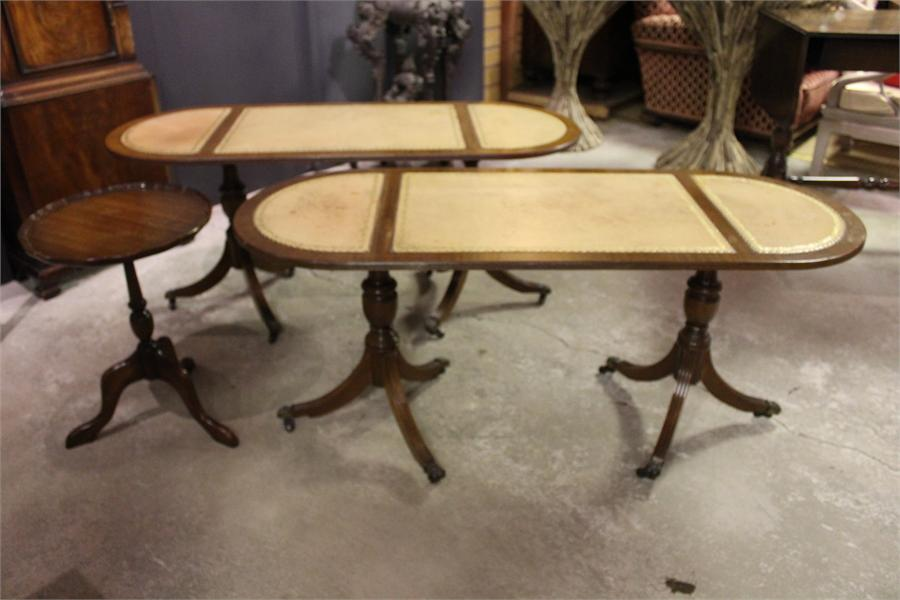 Lot 110 - A Pair of Modern leather topped pedestal coffee tables, with brass paw castors and a small
