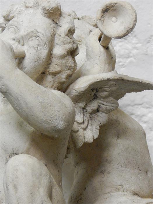 Lot 18 - A pair of stone-effect resin sitting cherubs / putti. Modern