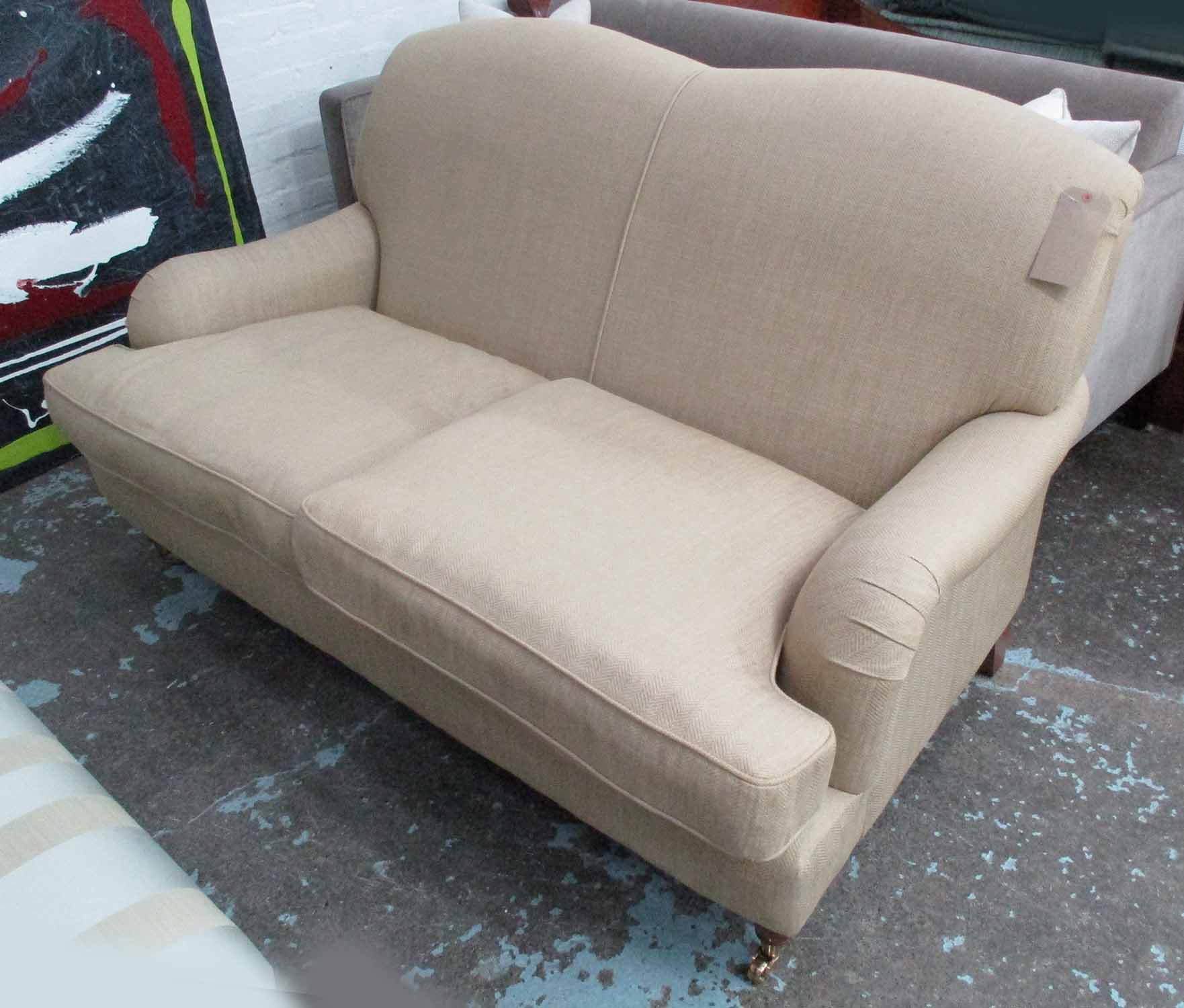 Lot 41 - LAURA ASHLEY SOFA, two seater, howard style, in brown herringbone fabric, on turned castor supports,