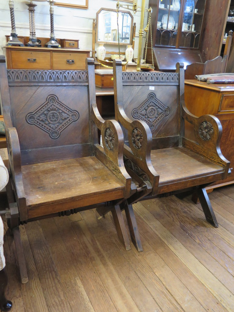 Lot 7 - A pair of Glastonbury type carved oak chairs, with lozenge carved backs and rosette carved arms (2)