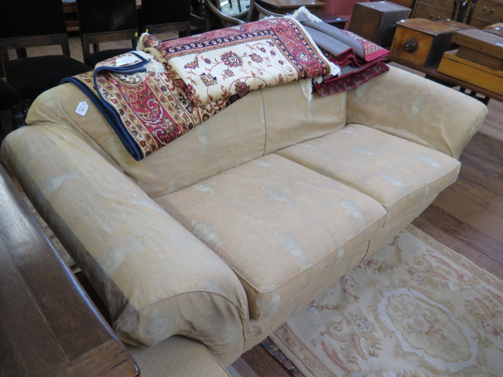 Lot 22 - A three seat settee, with scroll arms and turned legs on brass caps and castors 213cm wide and an