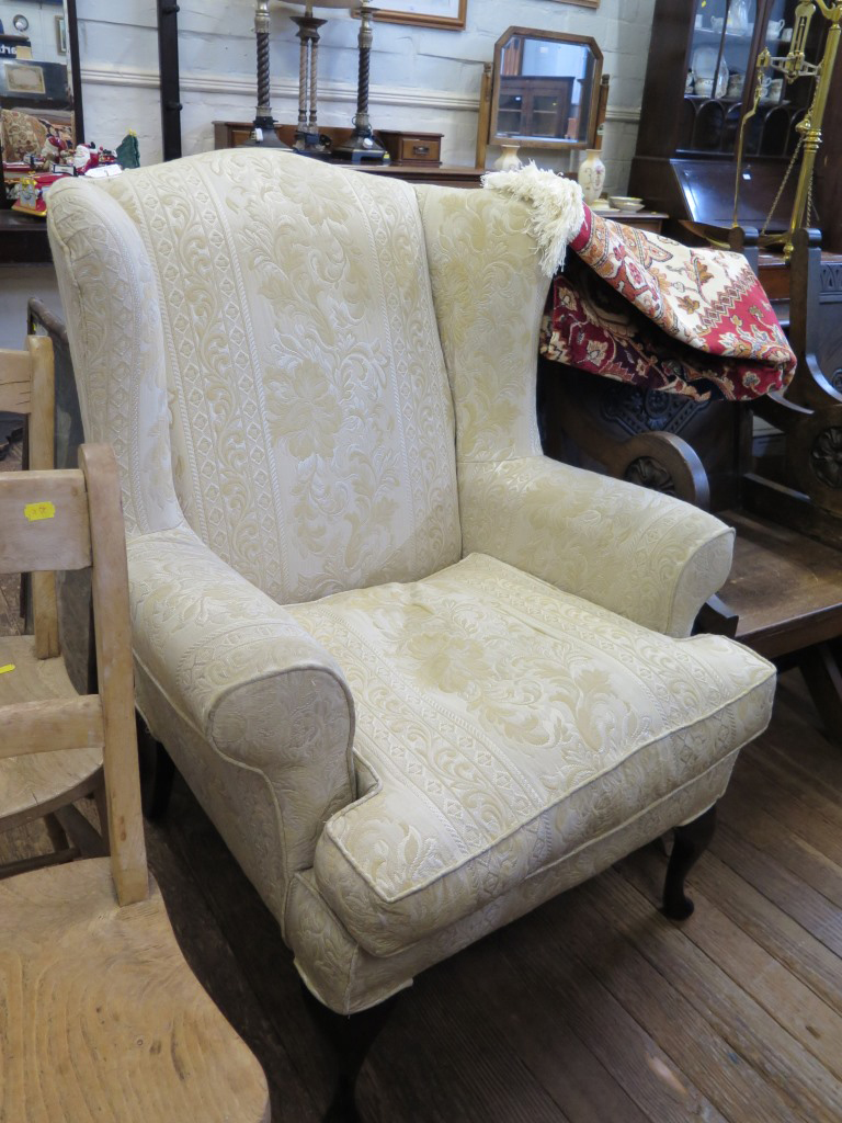 Lot 5 - An upholstered wing armchair, with cabriole legs