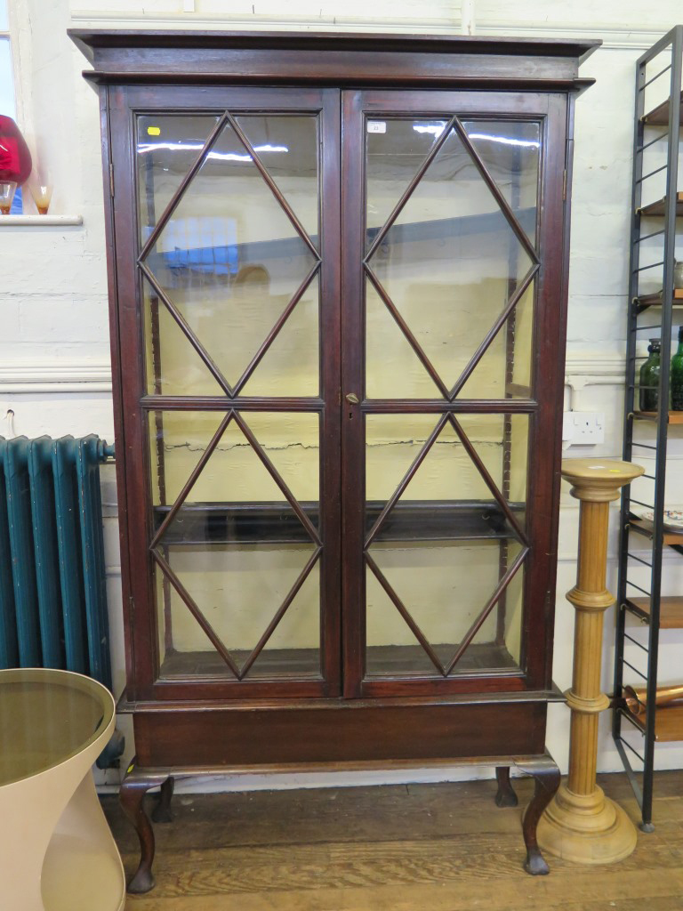Lot 23 - A stained beech bookcase, with twin glazed doors on a base with cabriole legs, 106cm wide