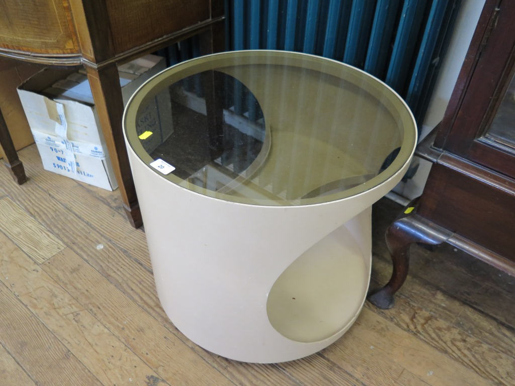 Lot 20 - A 1970s fawn plywood circular occasional table, with glass top and concave shelves 54cm diameter