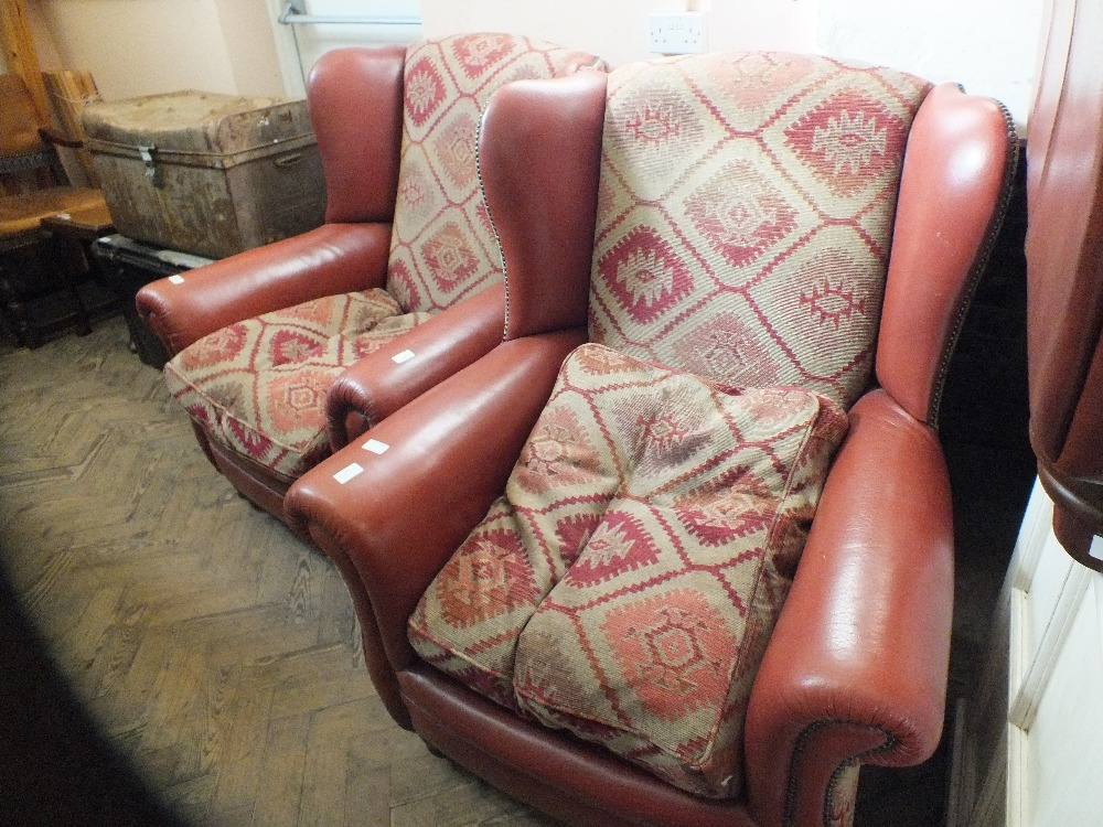 Lot 1033 - A pair of brown leather and cloth armchairs