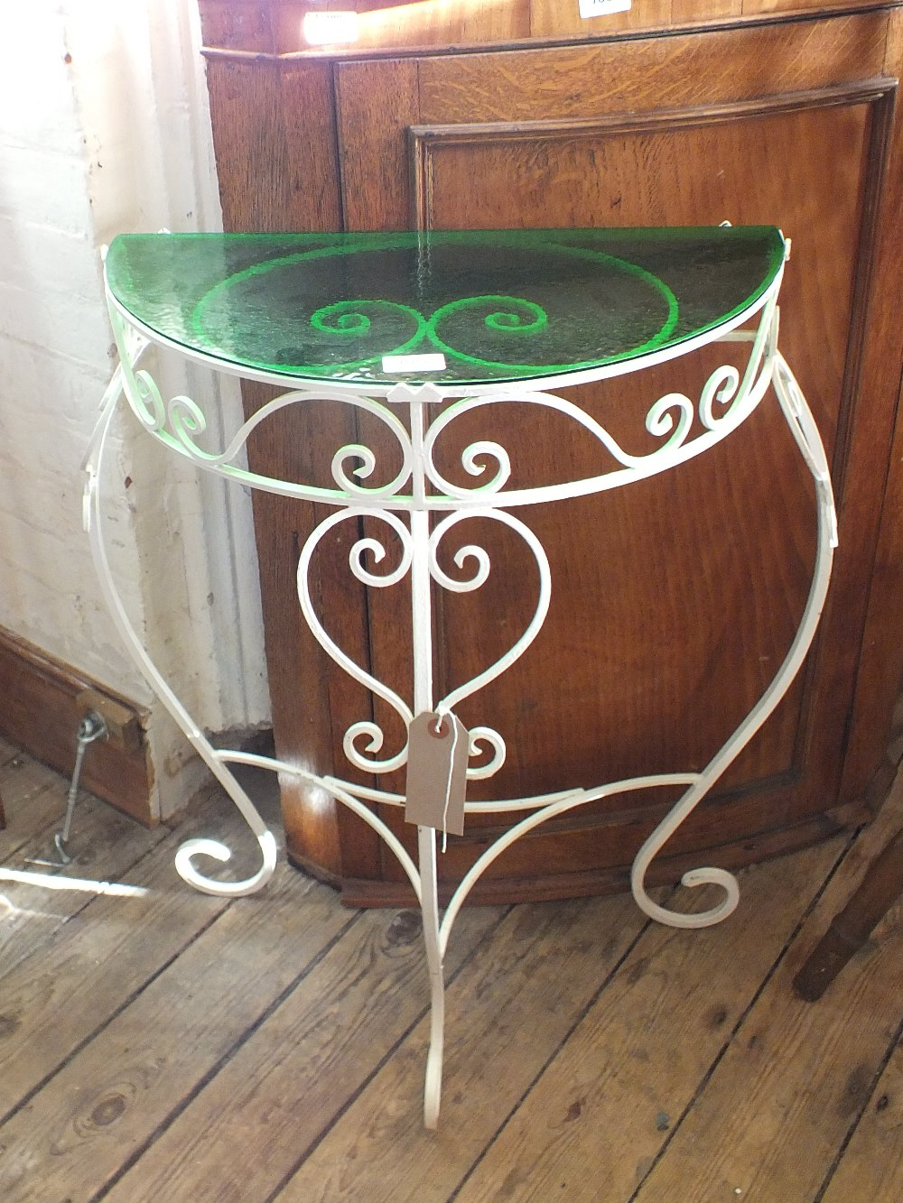 Lot 1050 - A painted iron half moon hall table with green glass top