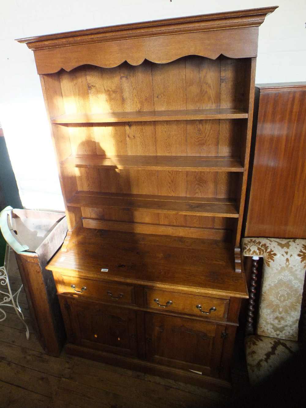 Lot 1053 - An oak shelf back dresser upon a two drawer two door base