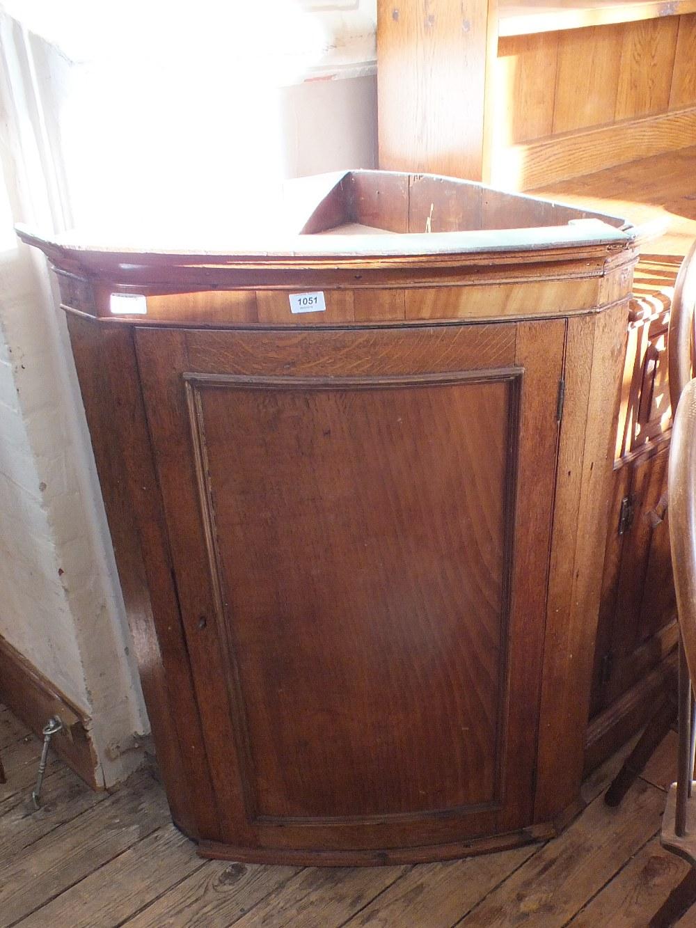 Lot 1051 - A 19th Century oak bow front corner cupboard