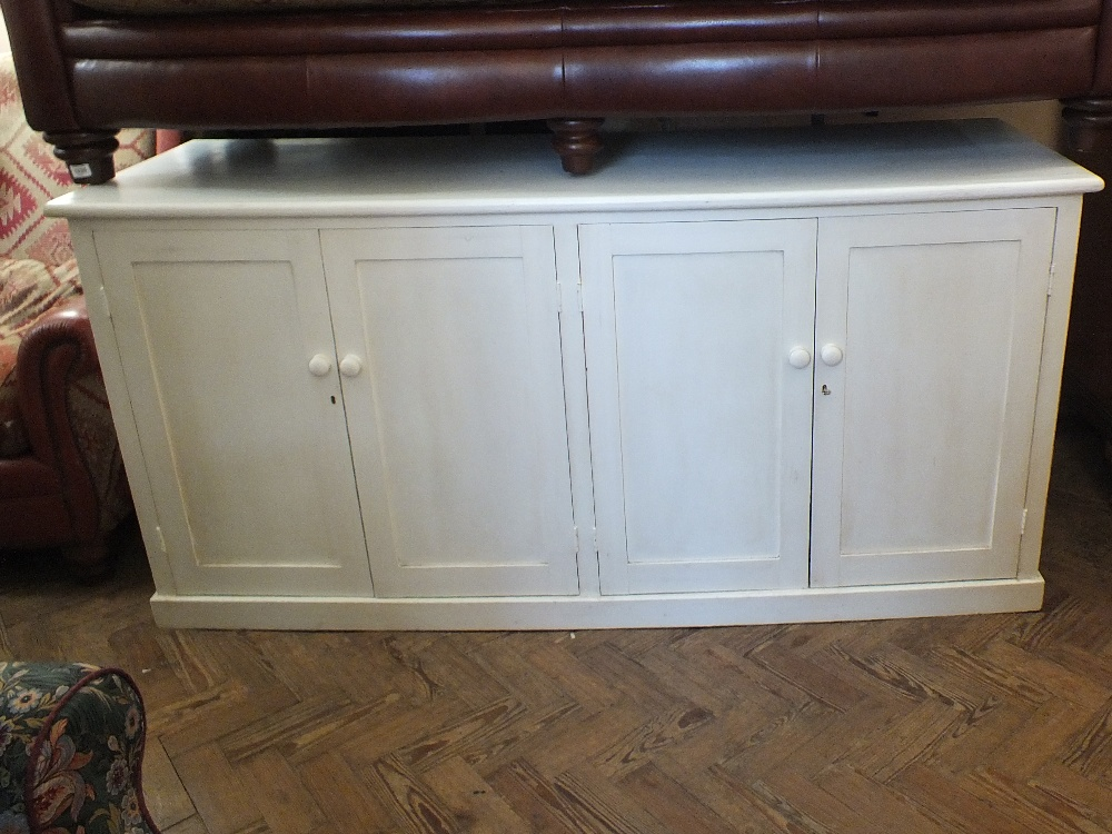 Lot 1034 - A white painted four door cupboard