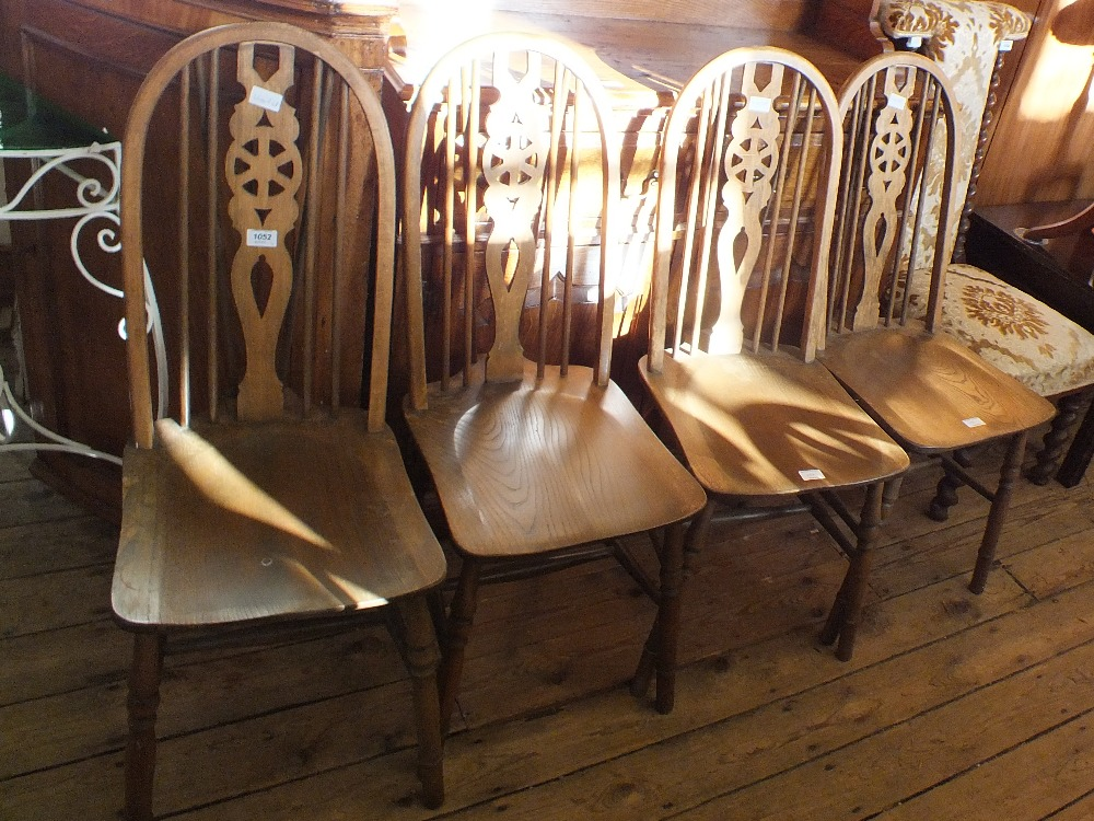Lot 1052 - A set of four wheel back dining chairs