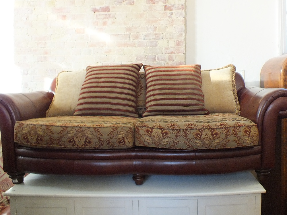 Lot 1035 - A brown leather and cloth three seater settee