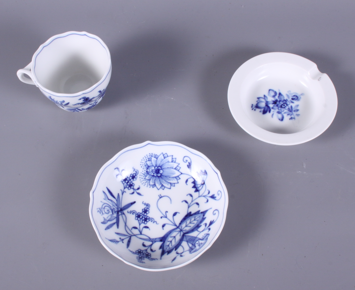 Lot 4 - A Meissen blue and white decorated coffee cup, a similar saucer and a similar ashtray
