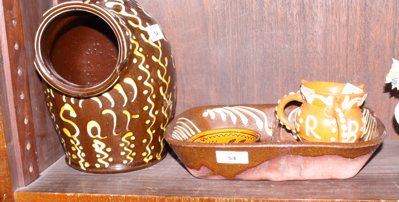 """Lot 54 - A slipware two-division dish, 11"""" wide, a similar three-handled tyg dated 1653, 3 1/2"""" high, and a"""