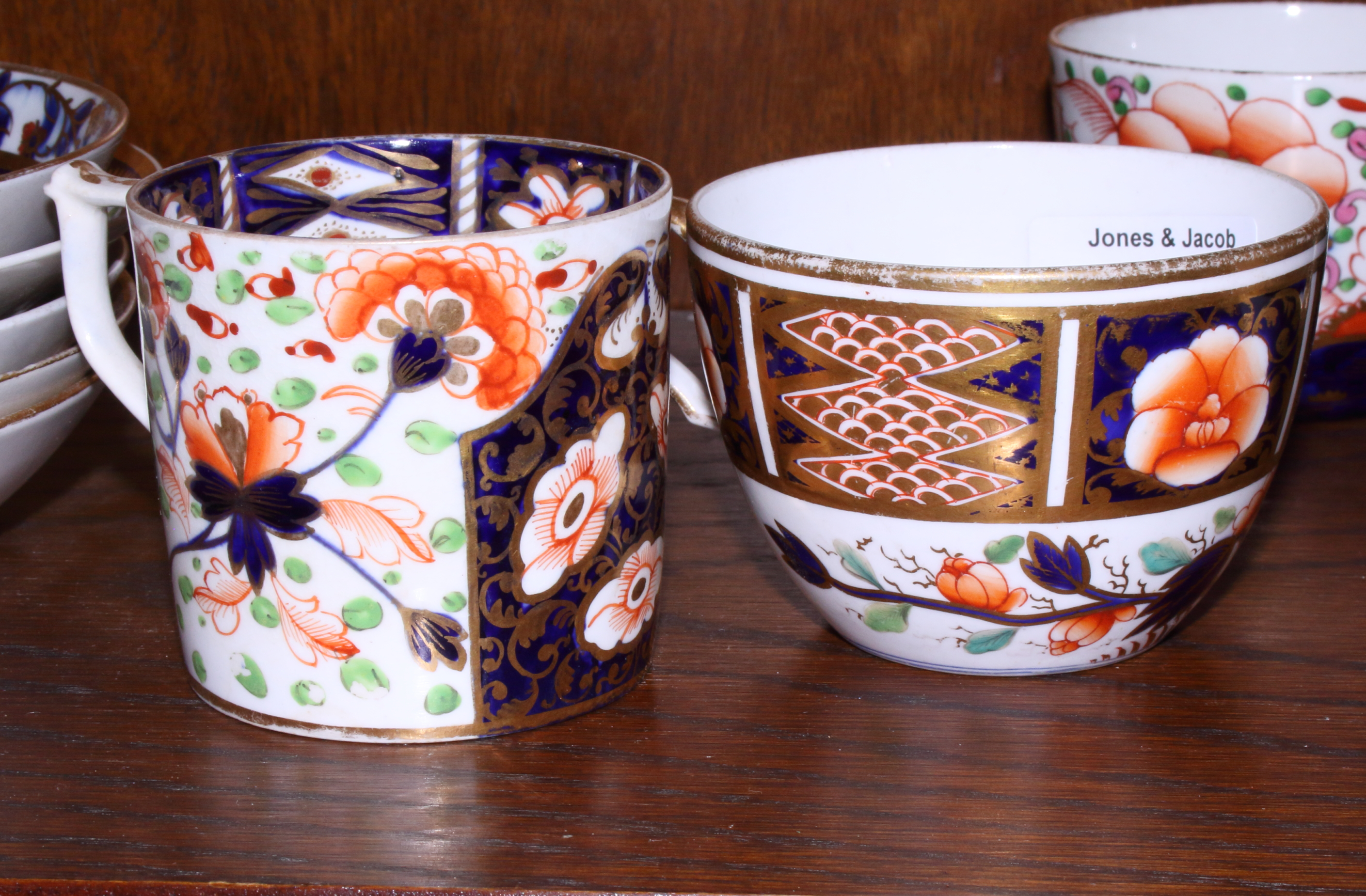 Lot 19 - Five early 19th century English porcelain cups and saucers, each decorated in the Imari palette,