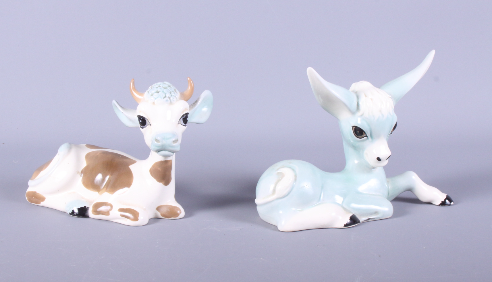 "Lot 8 - A Studio Szeiler recumbent cow and a companion donkey, 7"" long"