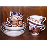 Five early 19th century English porcelain cups and saucers, each decorated in the Imari palette,