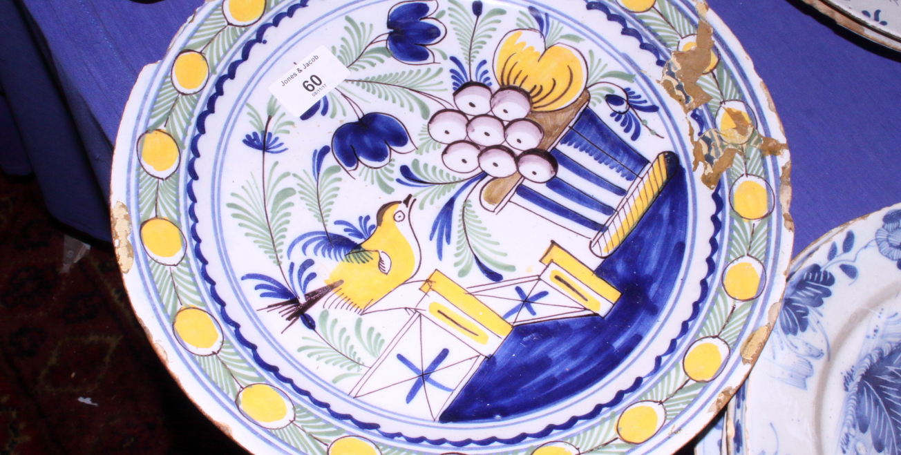 Lot 60 - A Delft pottery blue and white charger decorated with sprays of flowers within a cross hatched