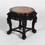 A Chinese dark wood jardiniere stand, Qing Dynasty, the shaped circular top with a mottled red and