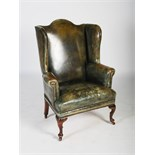 A 19th century oak and green leather upholstered wing armchair, with brass studded detail, raised on