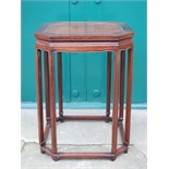 A Chinese dark wood octagonal shaped urn stand, the panelled top raised on eight tall legs united by