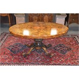 A Victorian walnut snap top loo table, the hinged oval top raised on a tapered cylindrical column
