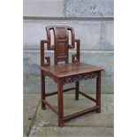 A Chinese dark wood chair, late Qing Dynasty, the rectangular panelled back carved in relief with