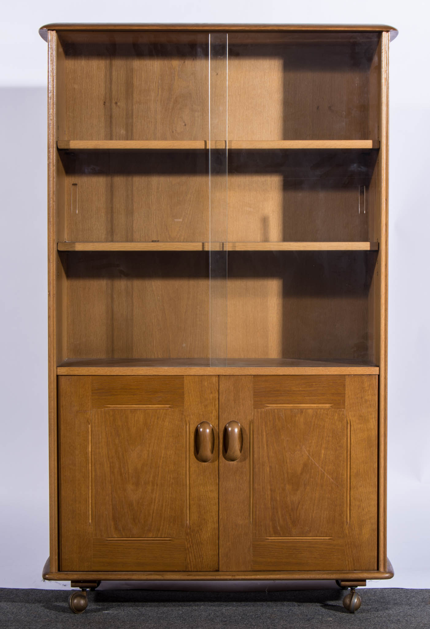 Lot 532  An Ercol Blonde Beech Bookcase Cabinet, Sliding Glass Doors  Enclosing Two Adjustable